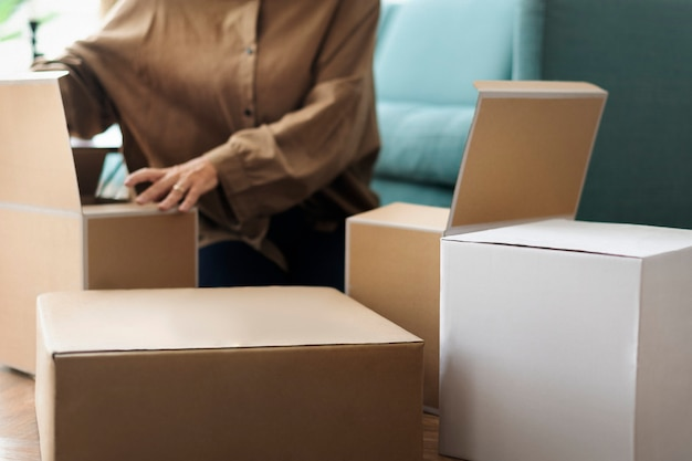 Kobieta rozpakowująca pudełka kraft w salonie
