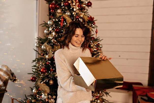 Kobieta rozpakowywanie prezentu bożonarodzeniowego