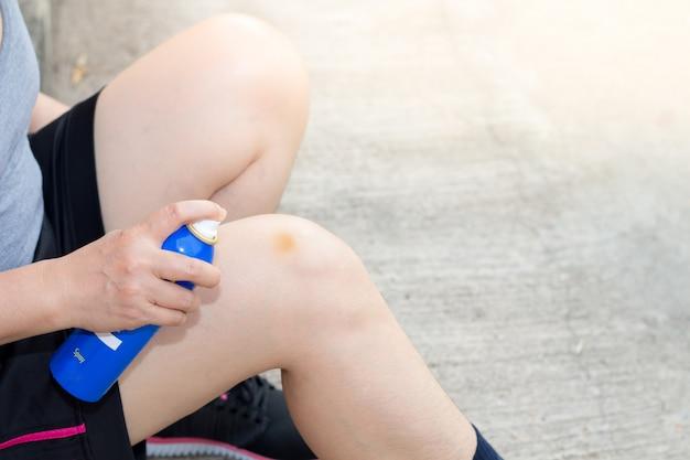 Kobieta rozpryskuje ból kolana i łokcia i czuje się źle na drodze między ćwiczeniami