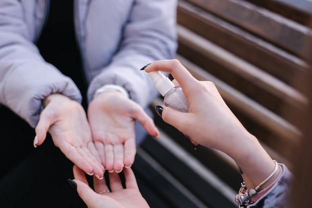Kobieta rozpyla środek dezynfekujący do rąk dla przyjaciela