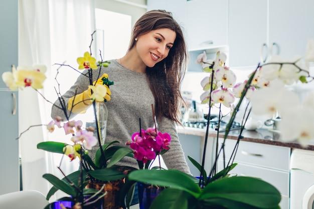 Kobieta rozpyla wodę na orchidee w kuchni. szczęśliwa gospodyni domowa dbająca o rośliny domowe i kwiaty.
