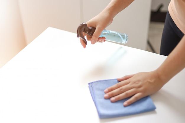Kobieta rozpylająca alkohol dezynfektant antybakteryjny. spray, aby zapobiec koronawirusowi lub covid-19.