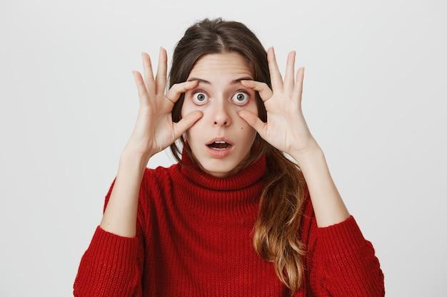 Kobieta rozszerza oczy dłońmi, patrzy pod wrażeniem