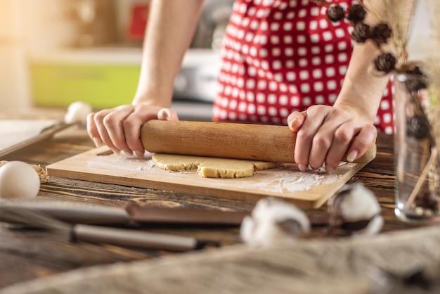 Kobieta rozwałkowuje surowe ciasto na drewnianym stole wałkiem, aby zrobić pyszne domowe ciasteczka w swojej kuchni