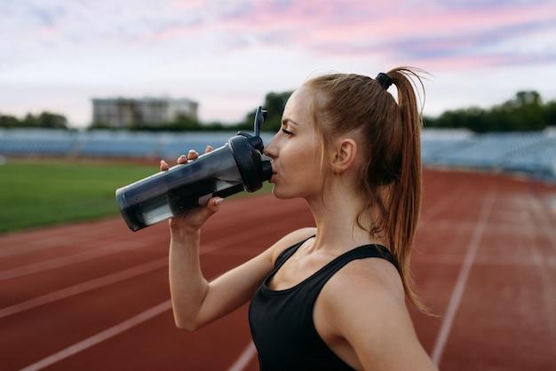 Kobieta runner w sportowej pije wodę, trening na stadionie. kobieta robi ćwiczenia rozciągające przed bieganiem na arenie na świeżym powietrzu