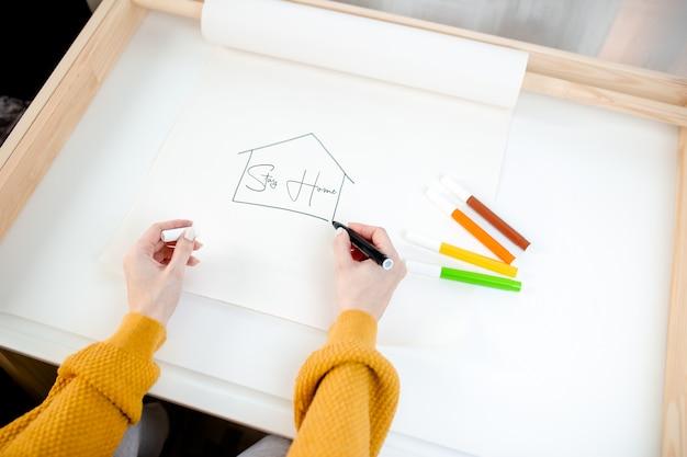 Kobieta rysunek na papierowej rolce na bielu stole. rysunek domu z kolorowymi markerami, pozostań w domu, zachowaj bezpieczeństwo podczas kwarantanny.