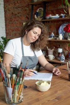 Kobieta-rzemieślnik pisze n notatnik, planuje dzień w dzienniku.