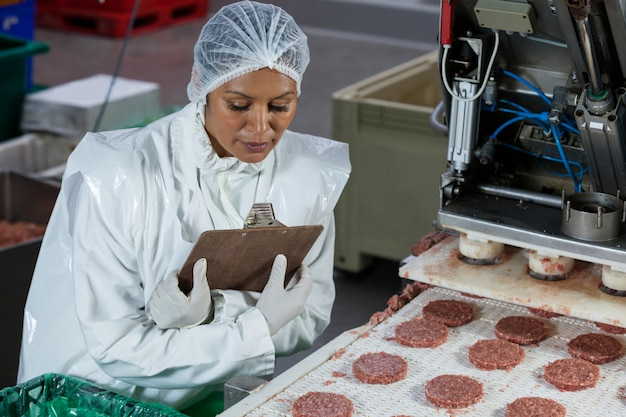Kobieta rzeźnik przetwarzania hamburger pasztecika