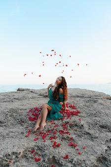 Kobieta rzuca czerwone płatki róż w pobliżu morza