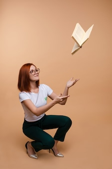 Kobieta rzuca książkę w powietrzu z czerwonym włosy.