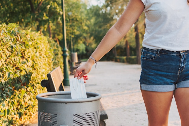 Kobieta rzuca maskę medyczną do kosza na śmieci w parku.