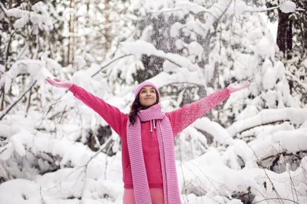 Kobieta rzuca śnieg w różowym ubraniu, kurtce, szaliku z dzianiny i czapce stoi zimą w zaśnieżonym lesie