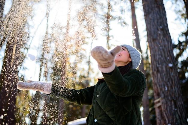 Kobieta rzuca w powietrze biały, luźny śnieg.