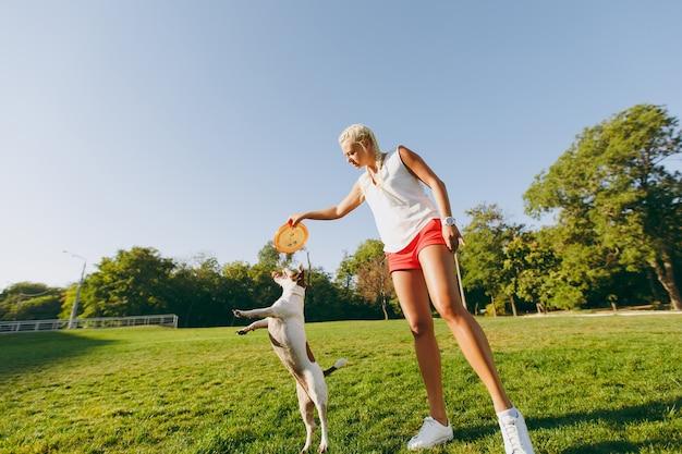 Kobieta rzucająca pomarańczowy latający dysk małemu zabawnemu psu, który łapie go na zielonej trawie. mały jack russel terrier zwierzak gra na świeżym powietrzu w parku. pies i właściciel na świeżym powietrzu.