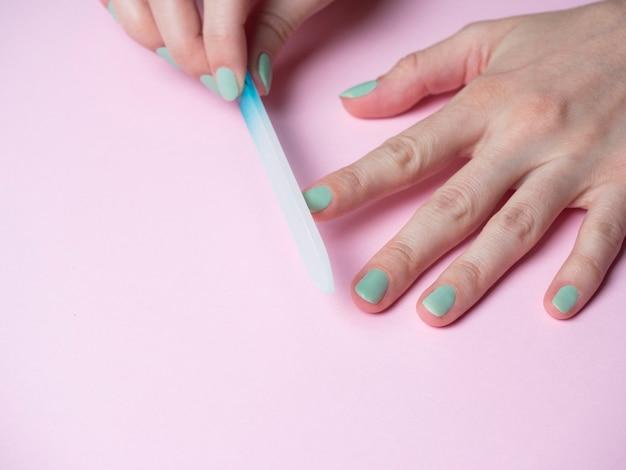 Kobieta sama piłuje paznokcie pilnikiem do paznokci na dłoni na różowym tle. pielęgnacja paznokci dłoni w domu. uroda i zdrowie