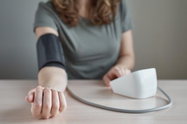 Kobieta sama pomiaru ciśnienia krwi z cyfrowym monitorem ciśnienia. pojęcie opieki zdrowotnej i medycznej
