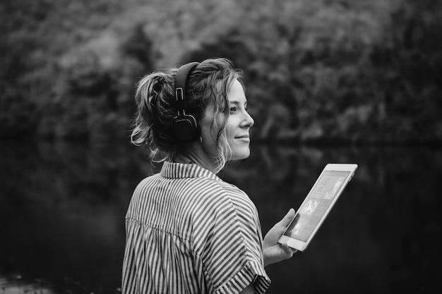 Kobieta sama w naturze słucha muzyki przez słuchawki i kopie