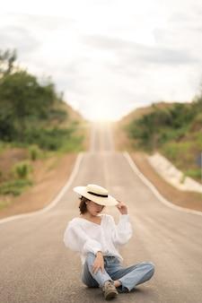 Kobieta sama w piękny pusty wiejski krzywej drogi asfaltowej