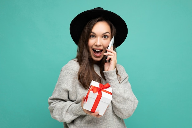 Kobieta samodzielnie na niebieskim tle ściana ma na sobie czarny kapelusz i szary sweter, trzymając pudełko rozmawia przez telefon komórkowy i patrząc na kamery.