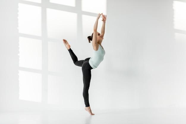 Kobieta samotnie ćwicząca gimnastykę artystyczną
