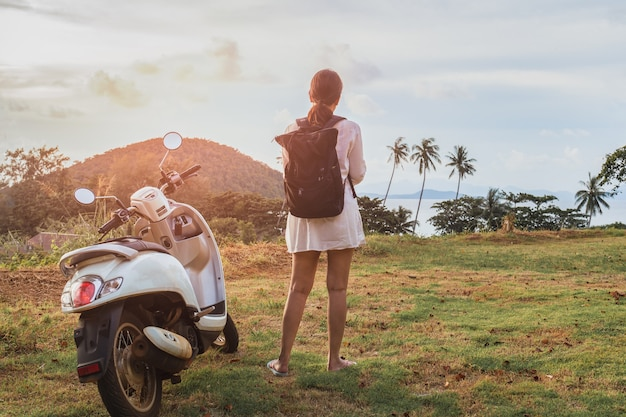 Kobieta samotnie stojąc w pobliżu motocykla na tropikalnej plaży.