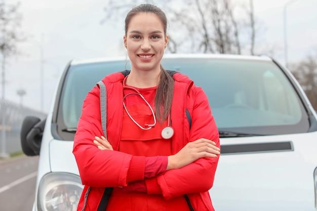 Kobieta sanitariusz w pobliżu samochodu pogotowia na zewnątrz