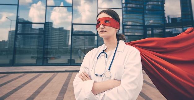 Kobieta sanitariuszka w płaszczu superbohatera stojącego na ulicy miasta. zdjęcie z miejscem na kopię.