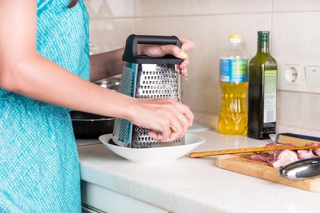 Kobieta ściera ser na tarce, aby wykorzystać go jako składnik gotowania podczas przygotowywania posiłku