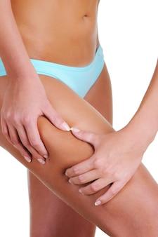 Kobieta ściska dłonie na biodrze, sprawdzając cellulit. część kobiecego ciała. widok z boku.