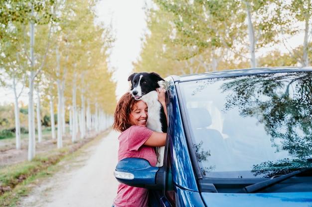 Kobieta ściska jej border collie psa w samochodzie dostawczym. koncepcja podróży