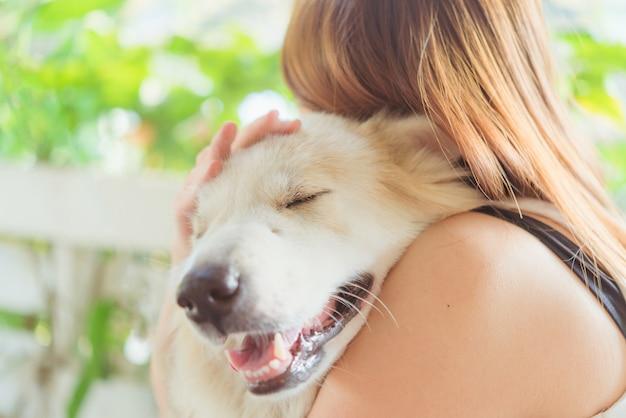Kobieta ściska jej psiego życzliwego zwierzęcego zbliżenia dużego psa, szczęścia i przyjaźni ,.