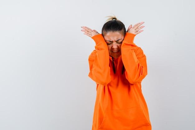 Kobieta ściskająca głowę z rękami w pomarańczowej bluzie z kapturem i wyglądająca na zirytowaną