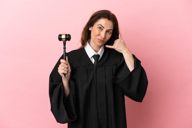 Kobieta sędzia w średnim wieku na białym tle na różowym tle co telefon gest. oddzwoń do mnie znak