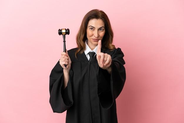 Kobieta sędzia w średnim wieku odizolowana na różowym tle pokazująca i unosząca palec