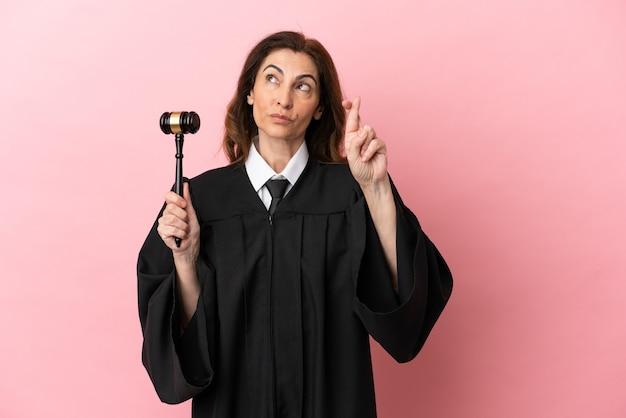 Kobieta sędzia w średnim wieku odizolowana na różowym tle z palcami skrzyżowanymi i życzącymi wszystkiego najlepszego