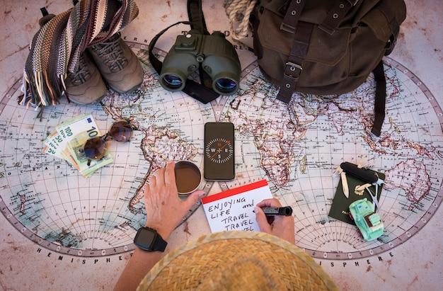 Kobieta seniorów planujących wakacyjną podróż na antycznej mapie świata popijając filiżankę czekolady. pieniądze i akcesoria podróżne - koncepcja aktywnej osoby w podeszłym wieku na emeryturze