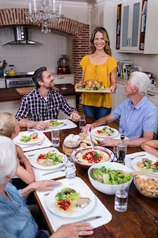 Kobieta serwująca jedzenie do swojej rodziny w kuchni