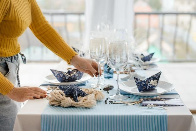 Kobieta serwująca przyjęcie w niebieskim kolorze z tekstylnym obrusem, białymi naczyniami, kieliszkami do wina i złotymi sztućcami. dekoracja urodzinowa. ścieśniać