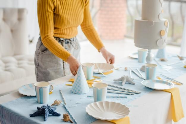 Kobieta serwująca przyjęcie w niebieskim kolorze z tekstylnym obrusem, białymi naczyniami, kieliszkami do wina i złotymi sztućcami. ozdoba z okazji urodzin.