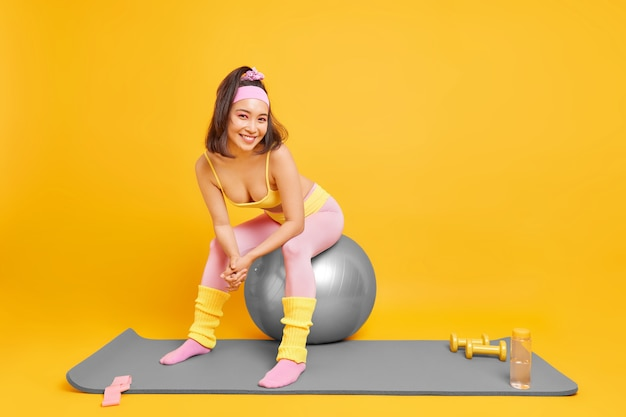 Kobieta siada na fitness piłka robi sobie przerwę po treningu ubrana w sportowe stroje uśmiecha się radośnie używa hantle opaska oporowa