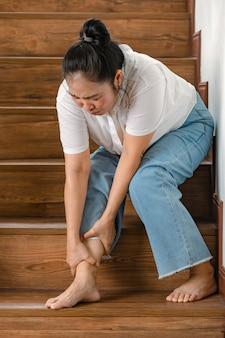 Kobieta siedząca, gdy nie może chodzić po schodach i zatrzymuje się, a następnie trzymaj nogi dla wsparcia i odpoczywaj z uczuciem mrowienia. pojęcie zespołu guillain-barre i choroby zdrętwiałych nóg lub efekt uboczny szczepionki.