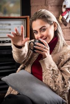 Kobieta siedząca i pijąca kawę