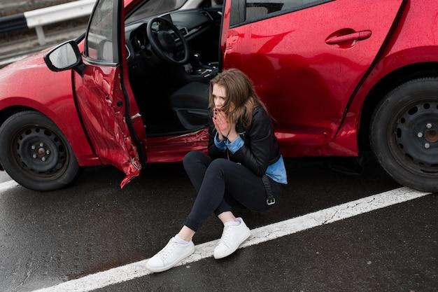 Kobieta siedząca na drodze po wypadku. ranna kobieta czuje się źle po wypadku samochodowym