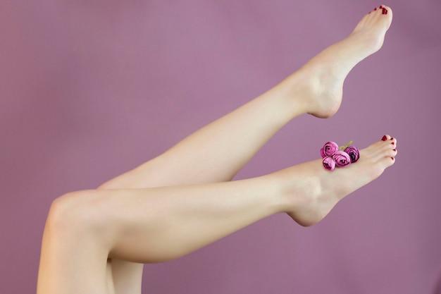 Kobieta siedząca na kanapie z wdzięcznie uniesionymi nogami - koncepcja piękna i pielęgnacji skóry. dosładzanie, depilacja. zdrowie stóp. smukłe, gładkie nogi