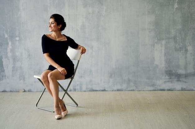 Kobieta siedząca na krześle w czarnej sukni pozuje moda luksus