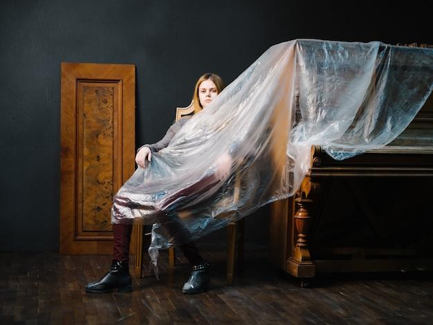 Kobieta siedząca na krześle w pobliżu romantyzmu wnętrza fortepianu