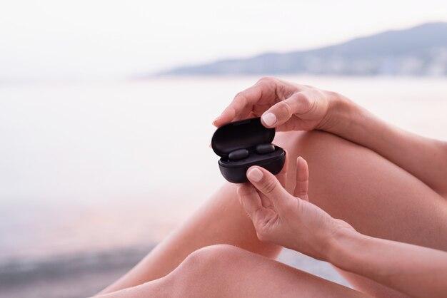 Kobieta siedząca na leżaku otwierająca pudełko z bezprzewodowymi słuchawkami, gotowa do słuchania muzyki