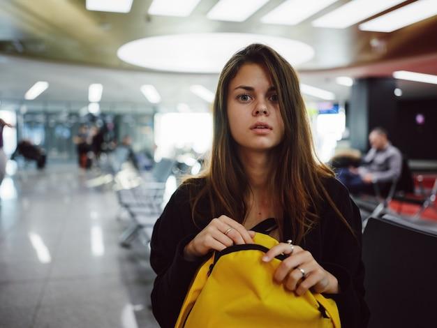 Kobieta siedząca na lotnisku w żółtym plecaku czekająca na lot