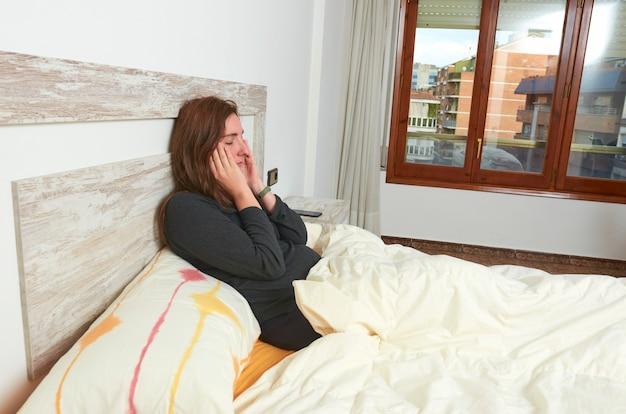 Kobieta siedząca na łóżku podrażniona. wczesne pobudki nie wystarczają do snu