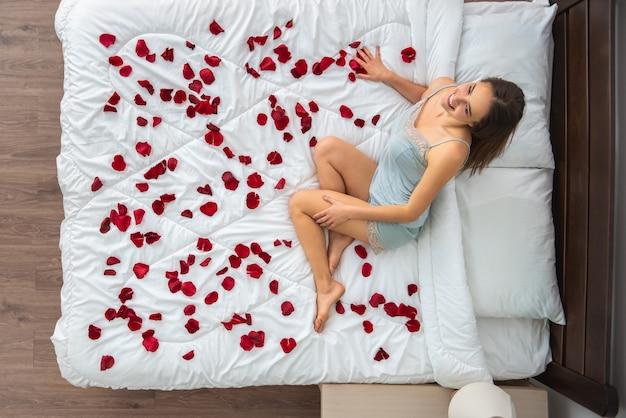 Kobieta siedząca na łóżku z płatkami róż. widok z góry